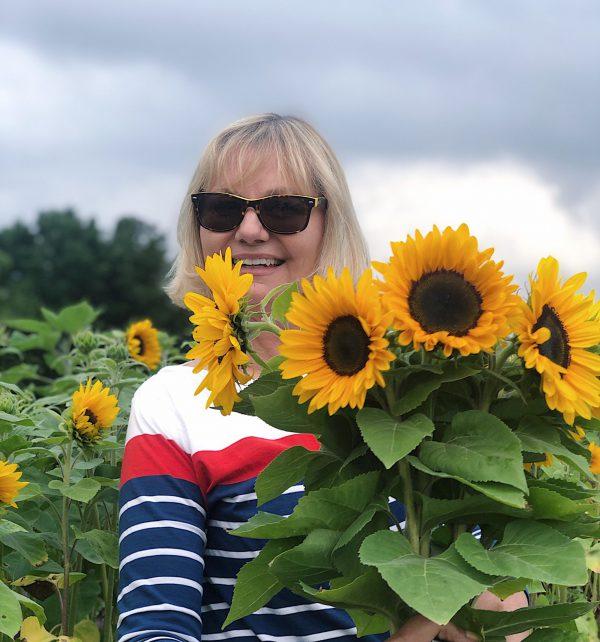 Blonde Frau im Sonnenblumenfeld mit blumenstrauss
